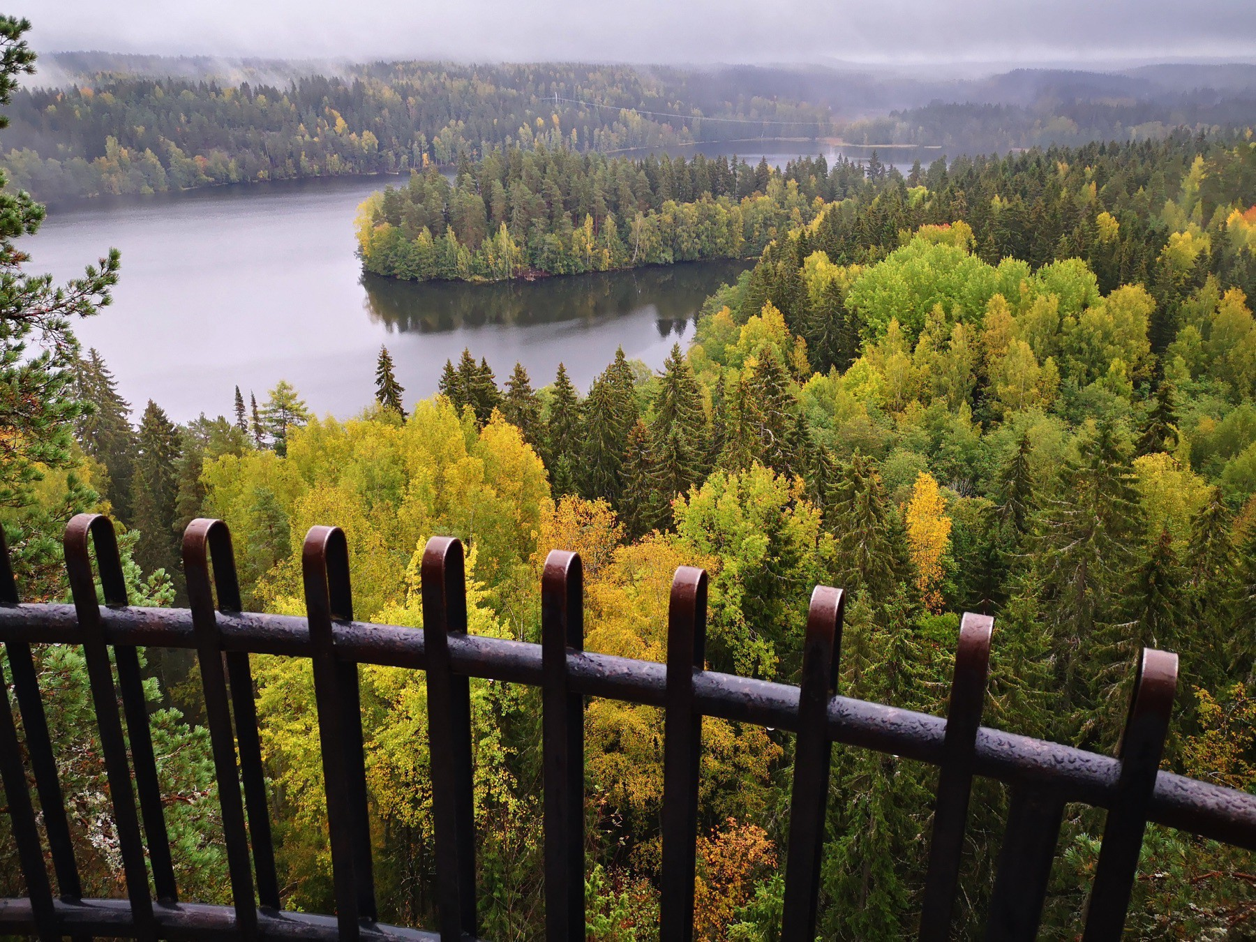 View over a lake in Southern Finland with some fog and fall foliage