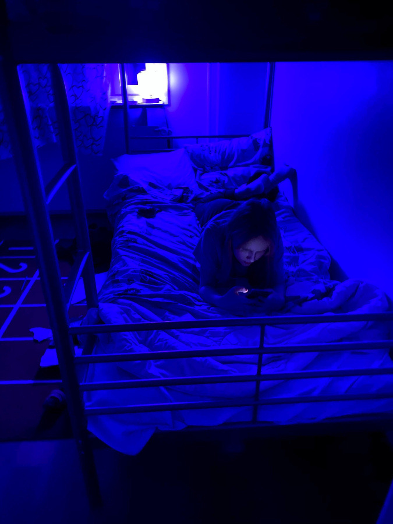 Blue lit room, bunk bed, a child on her phone