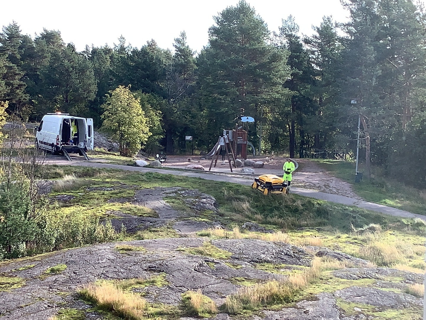 A park, with playground, rocks, a van and a robot lawn mower