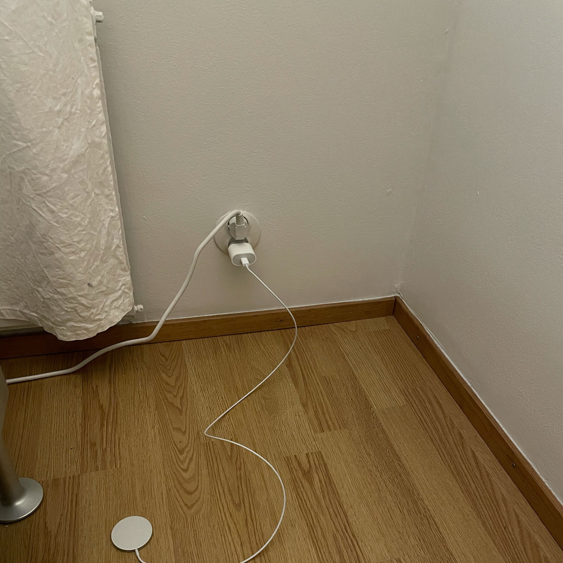 faux wooden floor, bed, magsafe charger on the floor