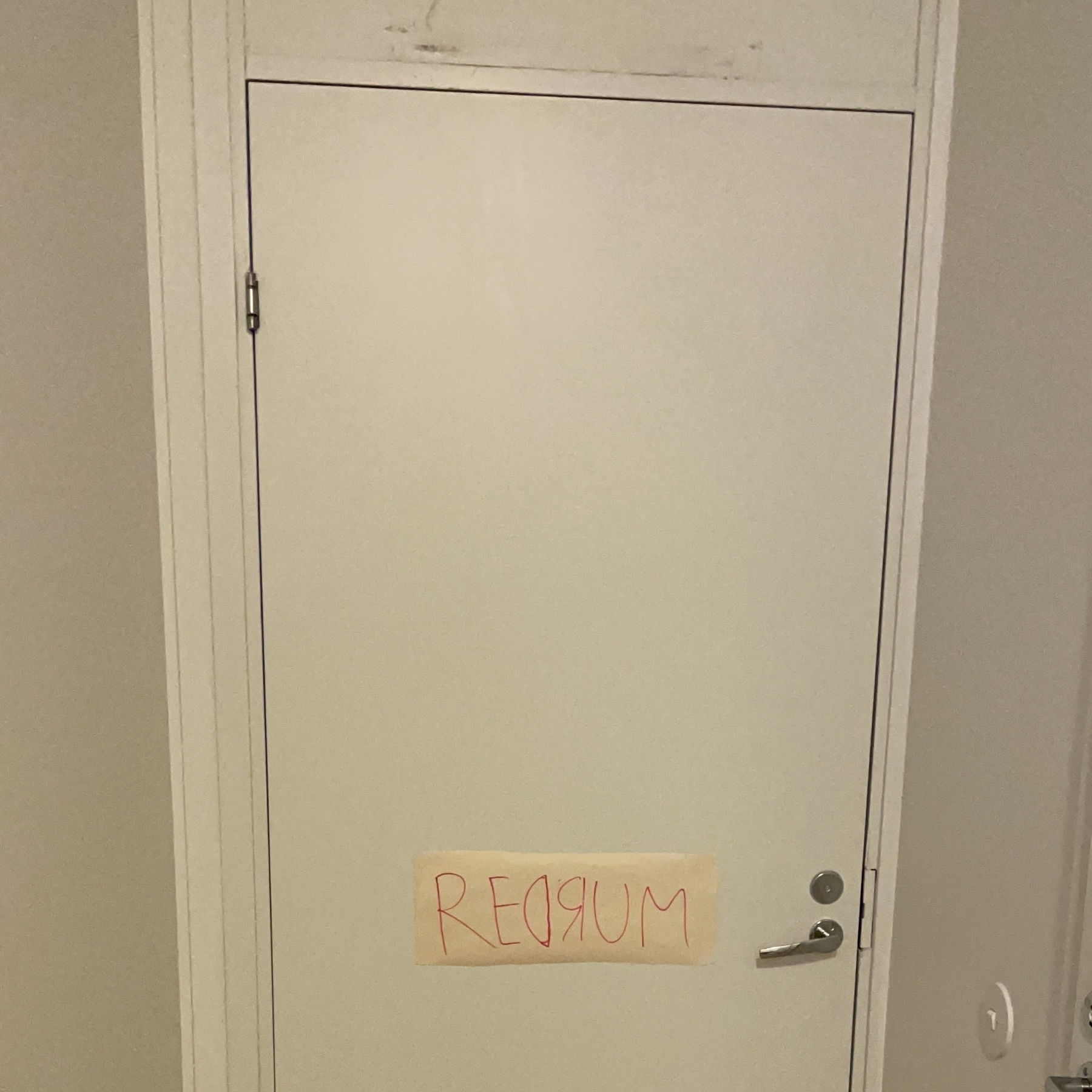 """white door with a note in red """"redrum"""""""
