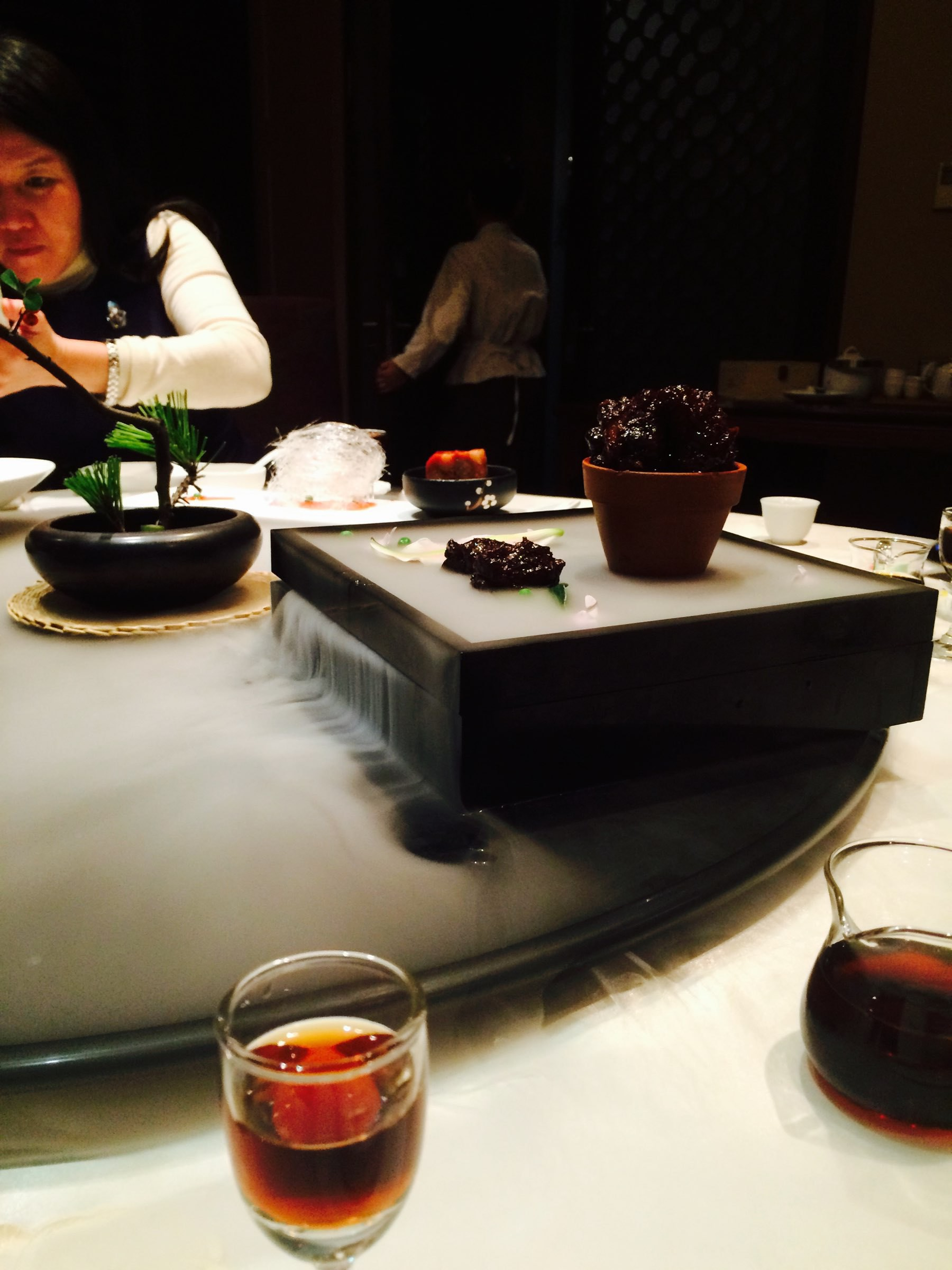 Chinese restaurant. Foreground: licquor in a glass. Further back: pork on a plate oozing dry ice