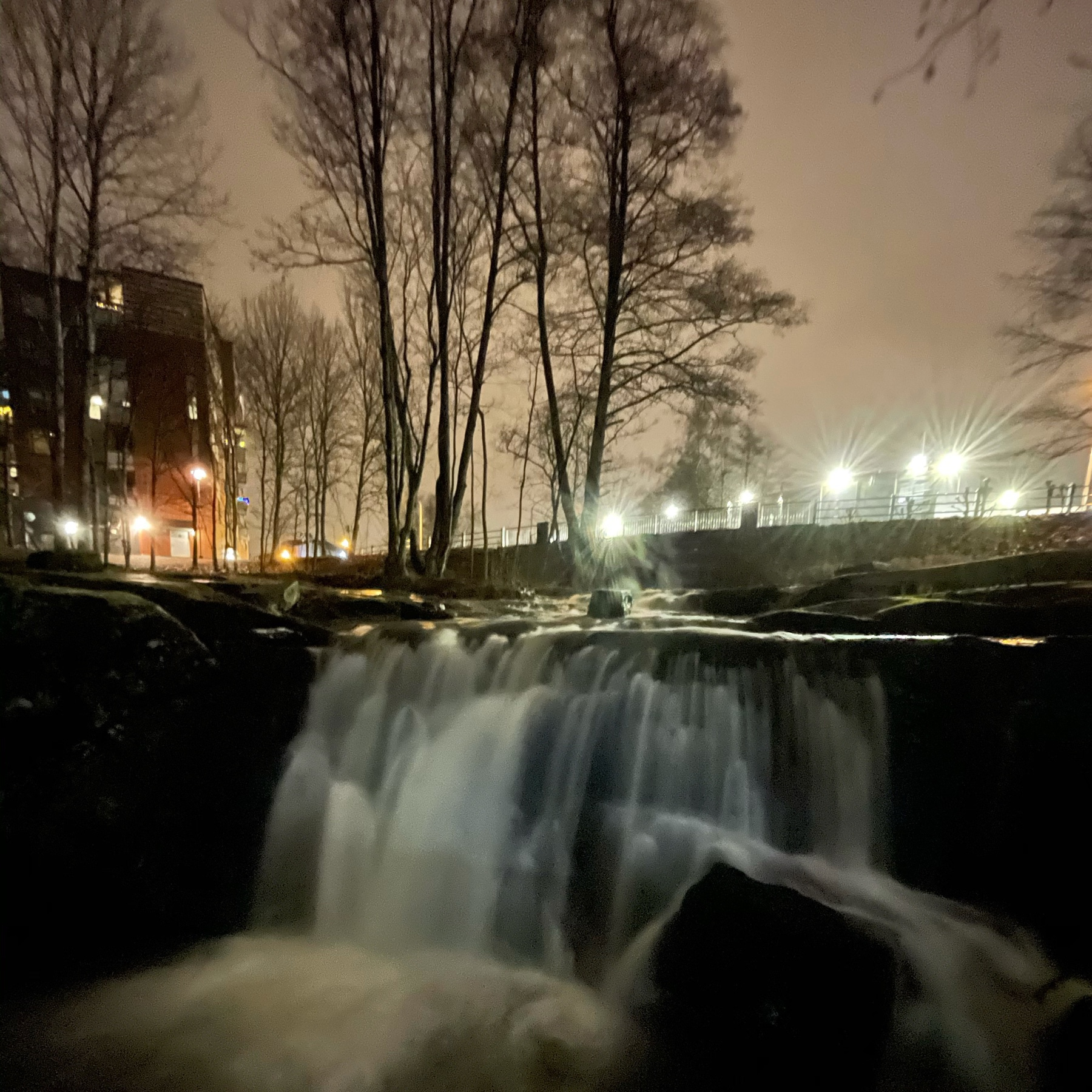 waterfall, street lights, a stone wall a bit further out and a steel railing