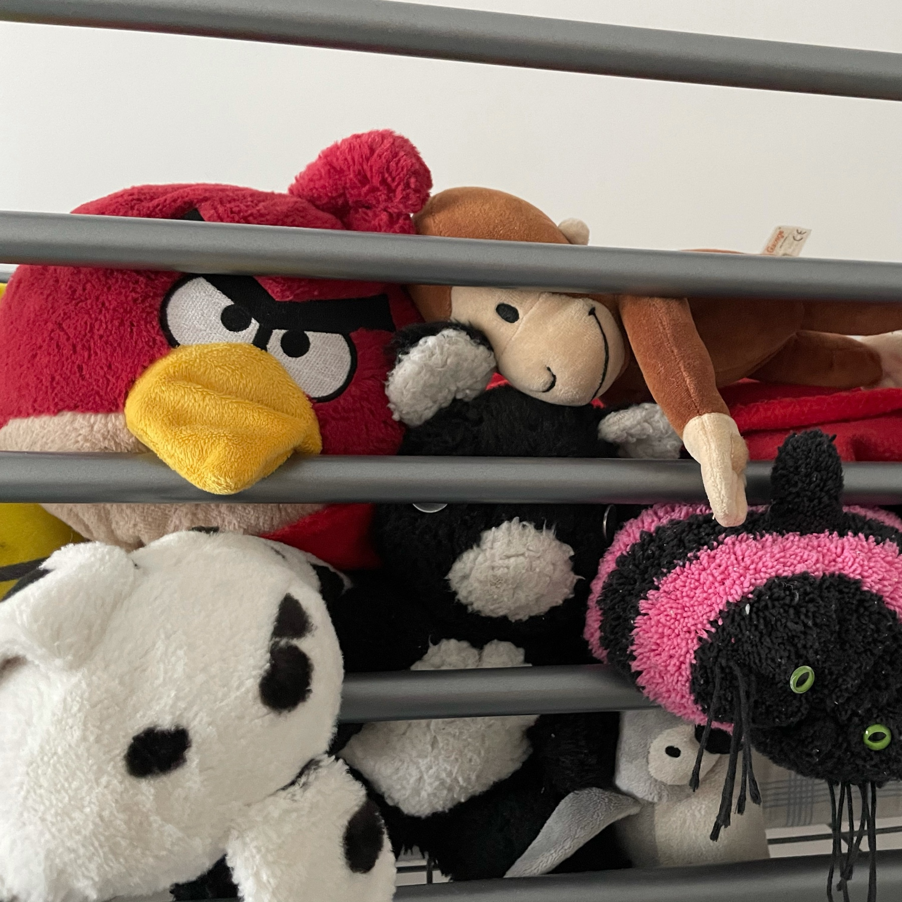 several teddy bears, dogs, monkey on a top bunk of a bunk bed