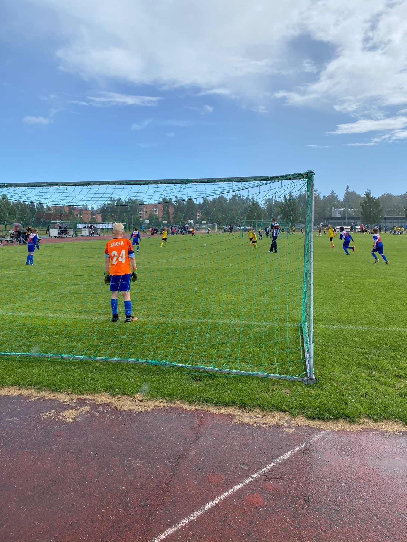 boy standing as a goal keeper in orange shirt, game going on further up field