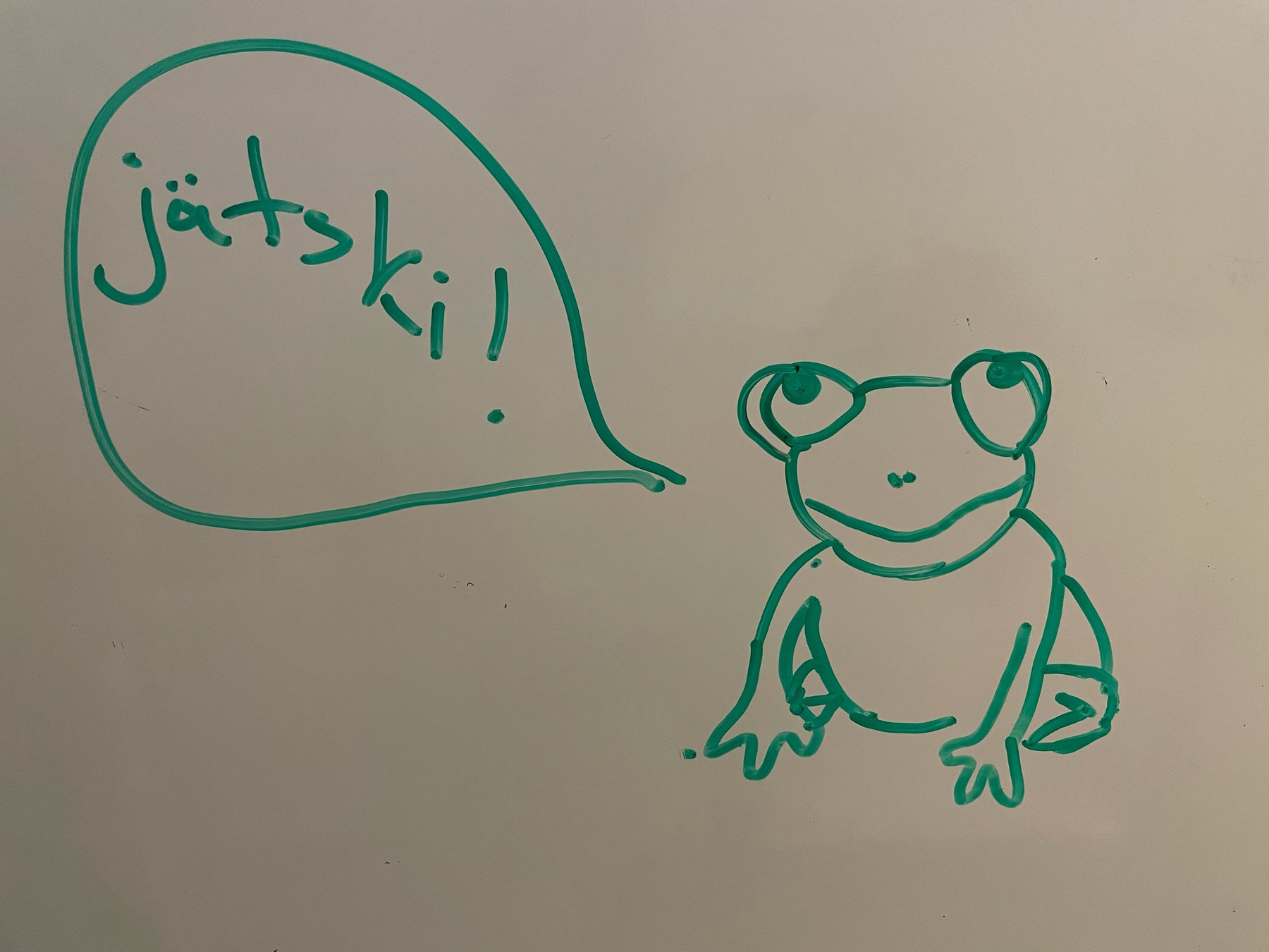 "frog drawn on whiteboard, speech bubble saying ""jätski"" i.e. ice cream"
