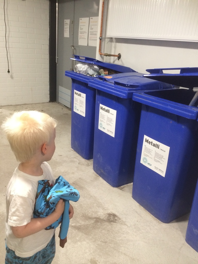 small boy and several trash cans in a concrete wall basement