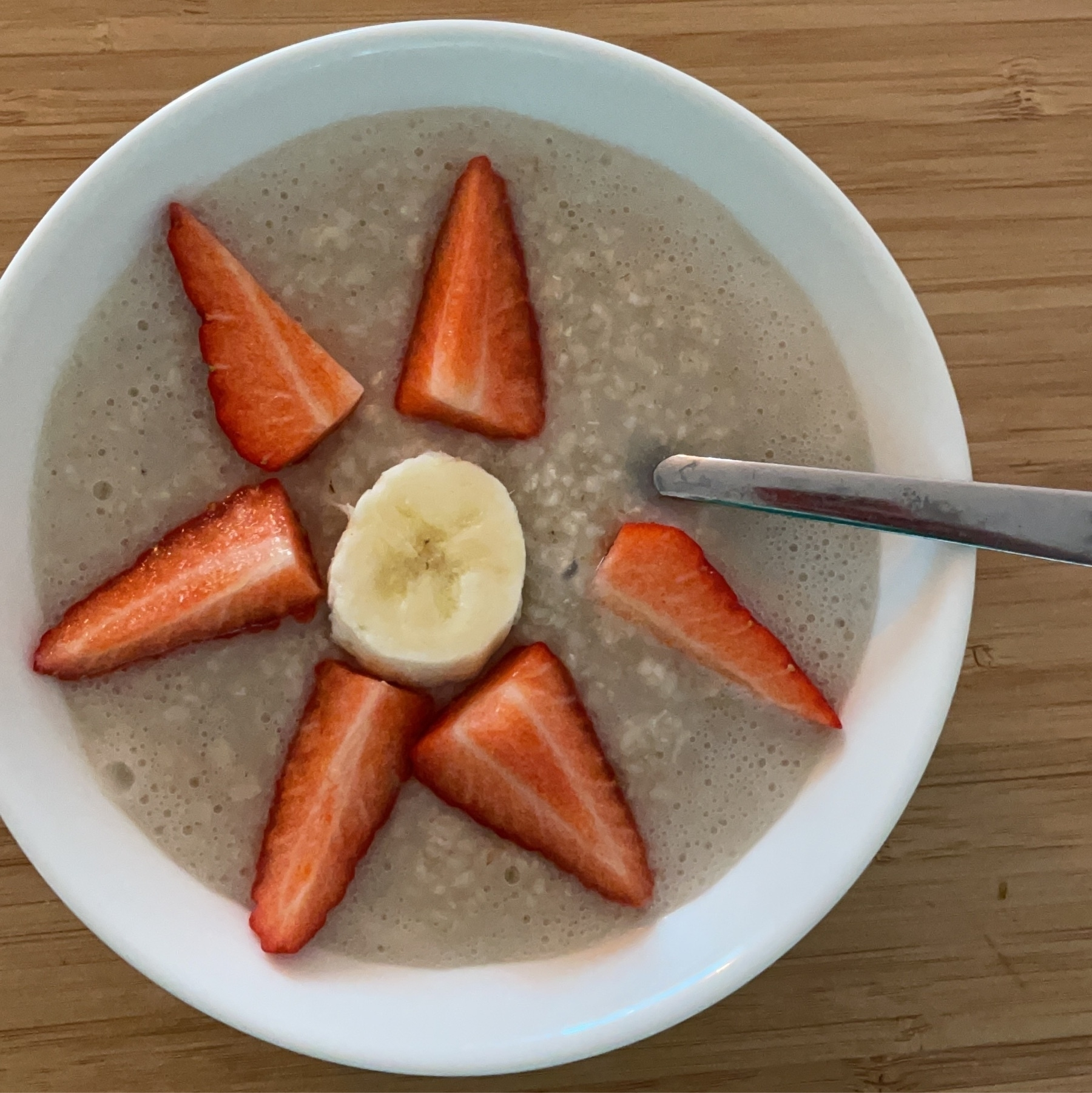 porridge with strawberries laid down in flower shape with a slice of banana in the middle