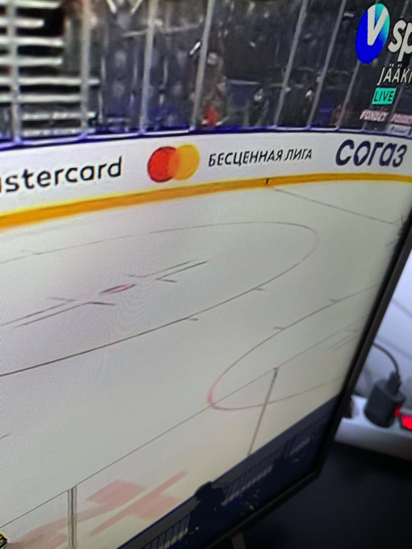 "mastercard ad on the side of a hockey rink saying ""priceless league"" in Russian"