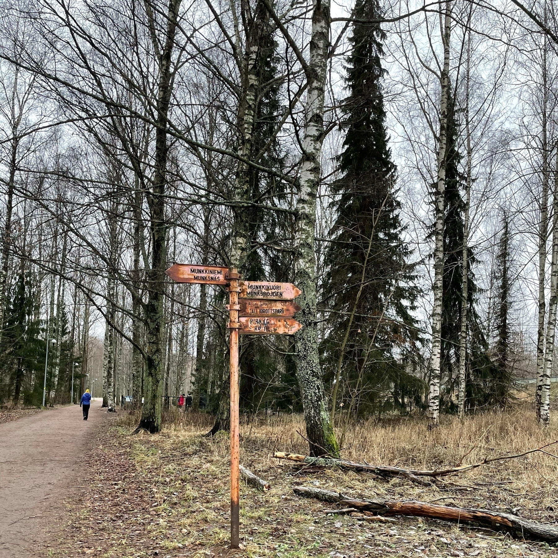 rusty signpost pointing to munkkiniemi and tali