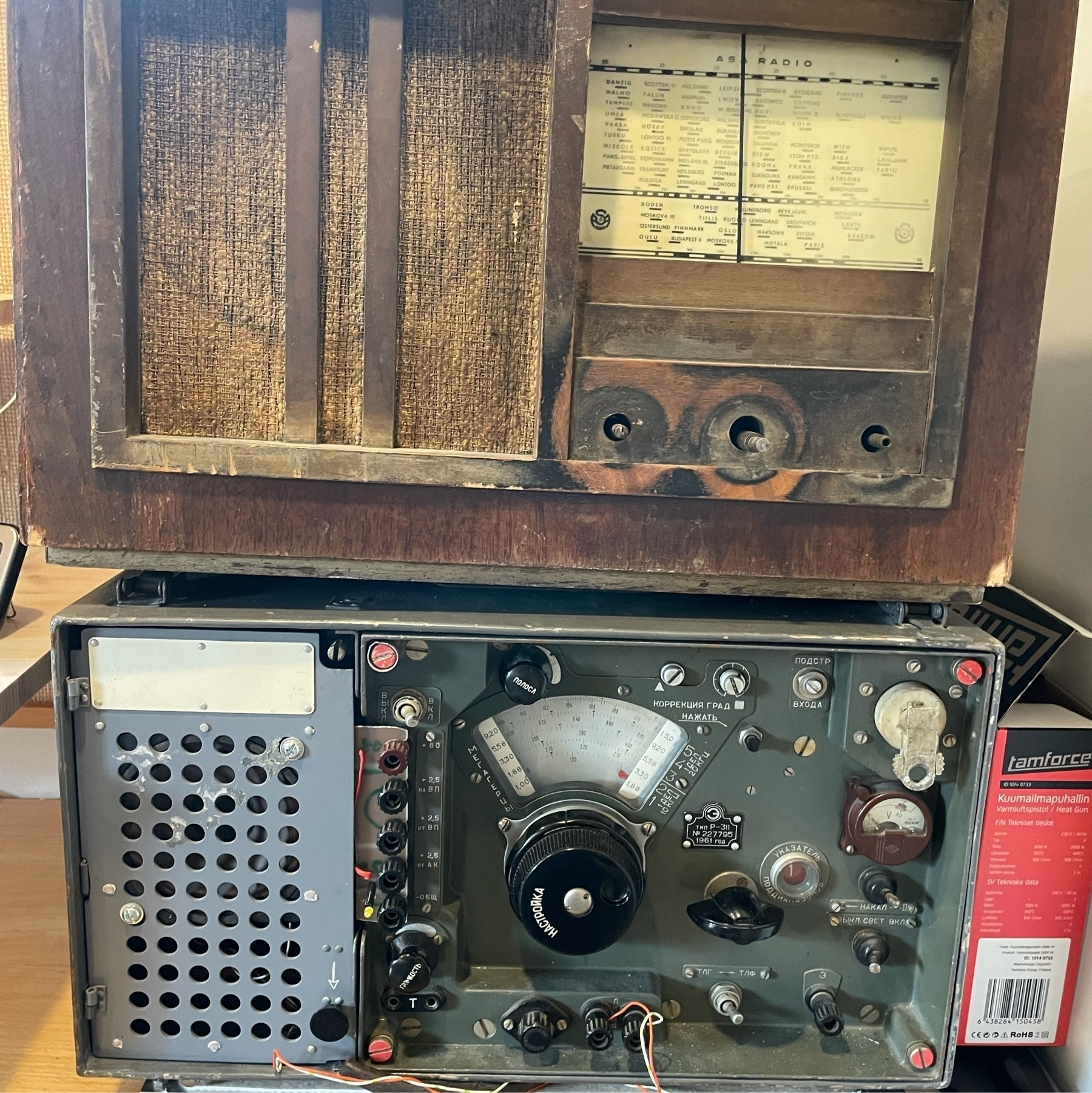 two old radios on top of each other, lower one with cyrillic texts in controllers