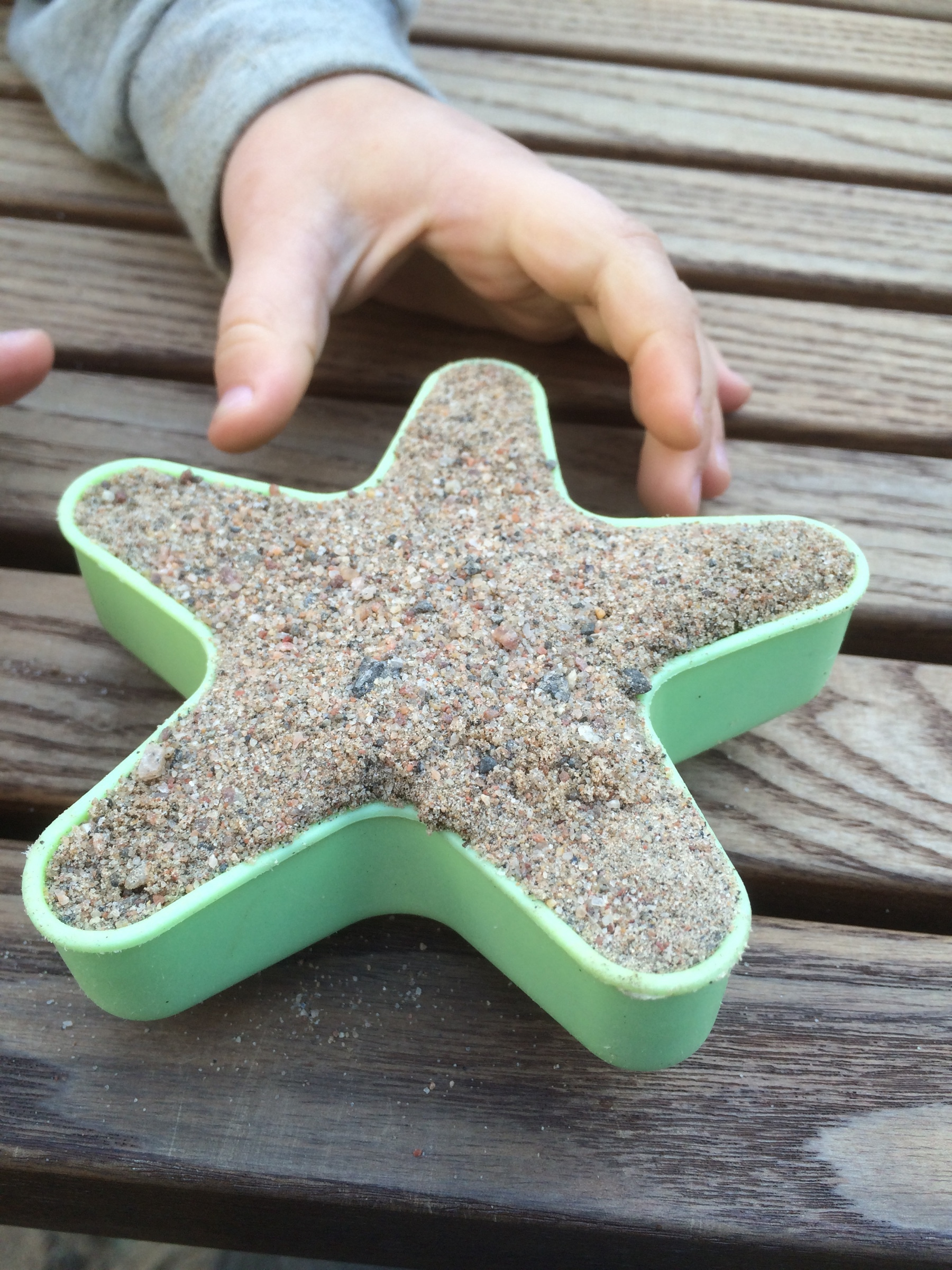 star shaped mold full of sand. delicious looking sand cake and a hand