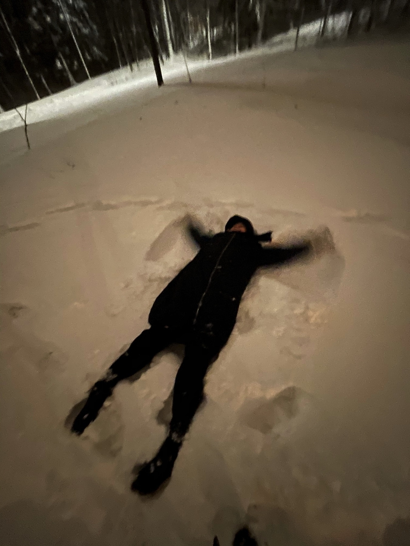 woman doing snow angels in deep snow