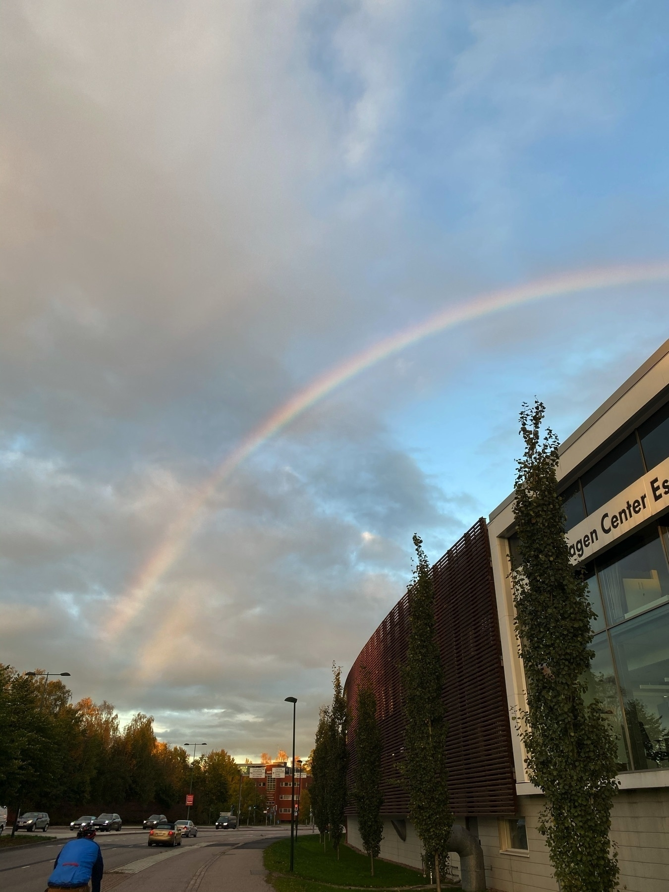 Car shop and multiple partial rainbows on sky