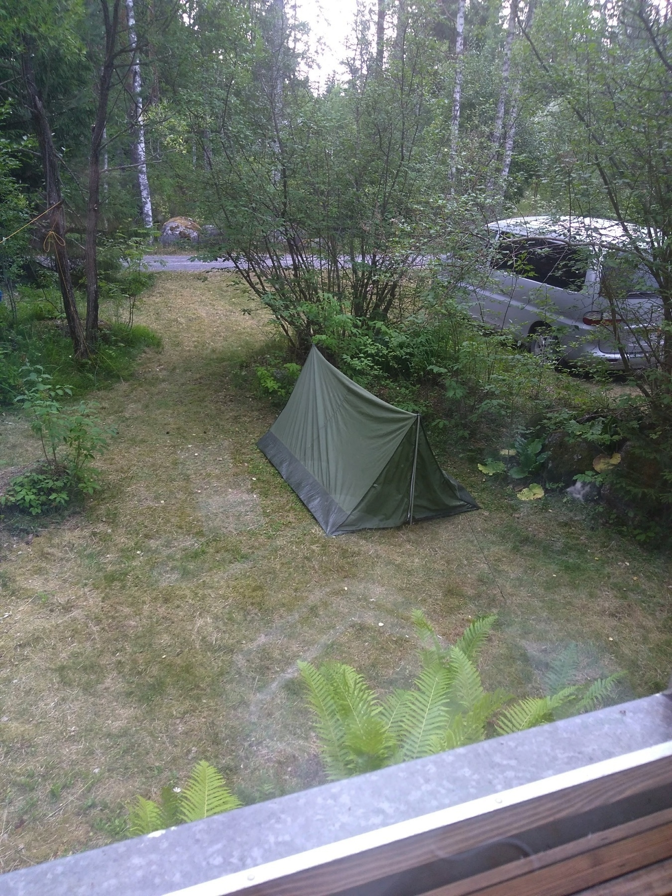 looking out from the window, a tent, a van, grass and some bushes in the garden