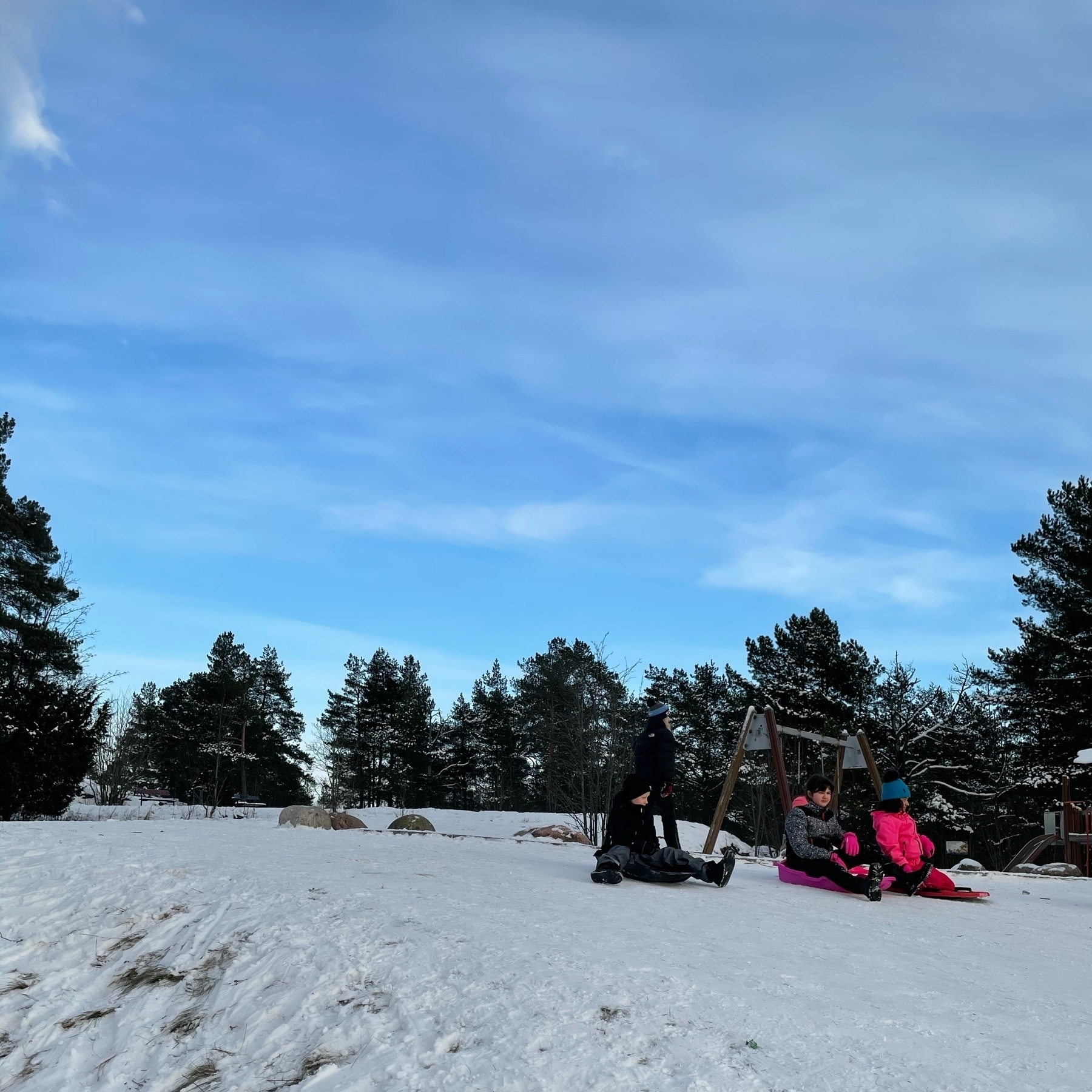 multiple kids waiting for their turn to slide down the hill